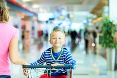 Happy cute boy at airport riding on luggage cart Stock Image