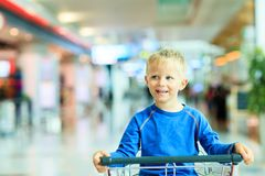 Happy cute boy at airport riding on luggage cart Stock Photo