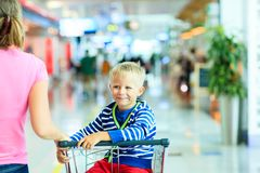 Happy cute boy at airport riding on luggage cart Stock Photography
