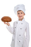 Happy cute boy in chef uniform holds a fresh bread, isolated on white background stock images