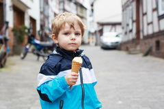 Happy cute boy eating ice cream in cone. Stock Photo