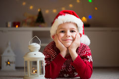 Happy cute boy lying on floor in red hat  and wait Santa Claus Royalty Free Stock Images