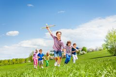 Happy cute boy with plane toy and chasing him kids Royalty Free Stock Photos
