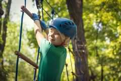 Happy cute boy playing at adventure park, holding ropes and climbing wooden stairs stock photos