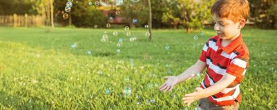 Happy boy playing with soap bubbles in the park. Happy cute boy playing to catch soap bubbles in the park Royalty Free Stock Photos