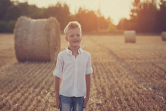 Happy cute boy playing in the wheat field on a warm summer day Royalty Free Stock Photo