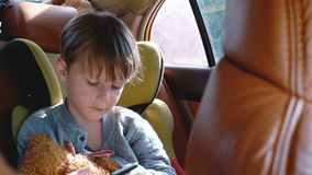 Happy cute little boy using smartphone entertainment app in car child safety seat, looking out the window on sunny day. Happy cute boy using smartphone stock video