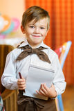 Happy cute boy waiter in apron writing order and. Looking at camera Stock Photo