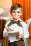 Happy cute boy waiter in apron writing order and. Looking at camera Royalty Free Stock Images