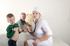 Happy cute boys playing with stethoscope in doctors office, hugging plush toy bear and smiling at camera. Female pediatrics. Copy Royalty Free Stock Photos
