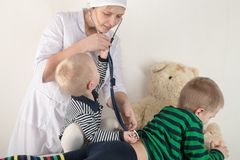 Happy cute boys playing with stethoscope in doctors office, hugging plush toy bear and smiling at camera. Female pediatrics. Copy Stock Images