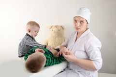 Happy cute boys playing with stethoscope in doctors office, hugging plush toy bear and smiling at camera. Female pediatrics. Copy Royalty Free Stock Image