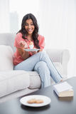 Happy cute brunette sitting on couch holding hard boiled egg Royalty Free Stock Photography