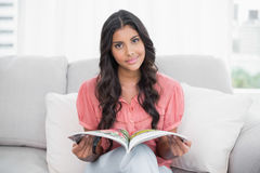 Happy cute brunette sitting on couch holding magazine Royalty Free Stock Photography