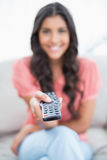 Happy cute brunette sitting on couch holding remote Stock Image