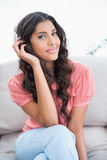 Happy cute brunette sitting on couch posing Royalty Free Stock Image