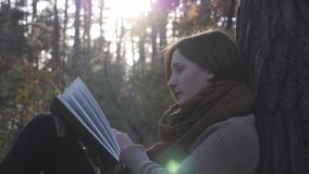 Happy Cute Brunette Woman Traveler Reading Book In Autumn Forest At Sunset. Female Tourist Relaxing And Enjoying Reading In Fall W Royalty Free Stock Photo