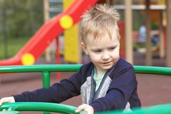Happy cute caucasian blonde baby boy on the children playground, smiling. royalty free stock photography