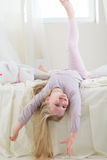 Happy cute child girl lying barefoot in the bed Royalty Free Stock Photography