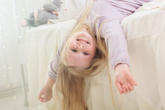 Happy cute child girl lying in the bed Stock Images