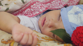 Happy cute child sleeping at flower outdoors in summer garden Stock Images