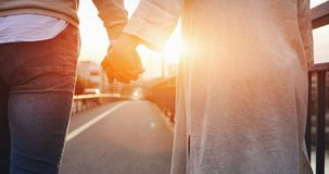 Happy couple holding hands in the sunset. Happy cute couple holding hands in the sunset Royalty Free Stock Image