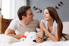 Happy cute couple looking at each other. Love relationship. Happy cute delighted couple looking at each other and smiling while lying on the bed royalty free stock photo
