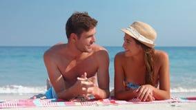 Happy cute couple speaking on towel stock video footage