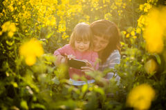 Happy cute daughter and mother on yellow field flowers Royalty Free Stock Photo