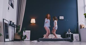 Happy cute daughter and young mother jumping and dancing on bed while have fun during holidays at home.  stock video