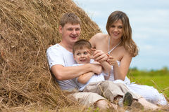 Happy cute family in haystack together summertime Royalty Free Stock Photography