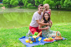 Happy cute family of three picnicking outdoor Stock Image