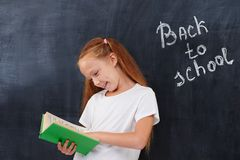 Happy cute ginger school girl looking in the book Royalty Free Stock Image