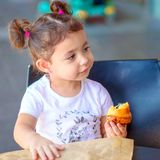 Happy cute girl on a cafe eating fresh croissant,on warm day. Zero waste, paper reusable packaging for grocery shopping. stock images