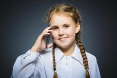 Happy cute girl with cell phone. isolated on gray Stock Photo