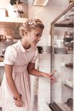 Happy cute girl choosing a cake to eat stock photography