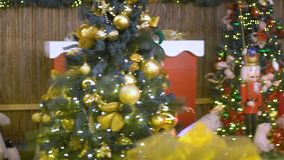 Happy cute girl in elf costume plays in Christmas area. Santa`s helper is playing with toys. Baby celebrates, rejoices. In Christmas, decorates the Christmas stock video