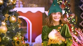 Happy cute girl in elf costume plays in Christmas area. Santa`s helper is playing with toys. Baby celebrates, rejoices. In Christmas, decorates the Christmas stock video footage