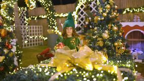 Happy cute girl in elf costume plays in Christmas area. Santa`s helper is playing with toys. Baby celebrates, rejoices. In Christmas, decorates the Christmas stock footage
