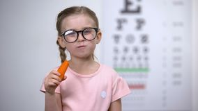 Happy cute girl in eyeglasses eating carrot, vitamin A for good vision, health. Stock footage stock video