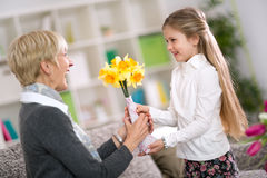 Happy cute girl giving flower her grandma Royalty Free Stock Photos