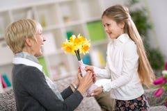 Happy cute girl giving flower her grandma Royalty Free Stock Photos