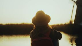 Happy cute girl in hat sits on sunset river pier. Golden hour. Enjoying wonderful travel moment. 4K back view close-up. Amazing sun lens flare. Silhouette shot stock video
