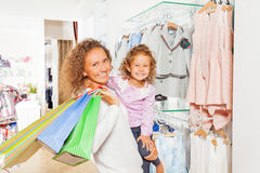 Happy cute girl with her mother holding bags Royalty Free Stock Photography