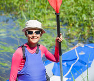 Happy cute girl holding paddle near a kayak Royalty Free Stock Image