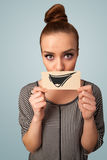 Happy cute girl holding paper with funny smiley drawing Royalty Free Stock Photo