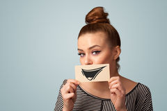 Happy cute girl holding paper with funny smiley drawing Stock Photo