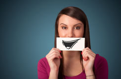 Happy cute girl holding paper with funny smiley drawing Royalty Free Stock Photos