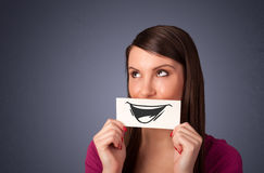 Happy cute girl holding paper with funny smiley drawing Stock Images