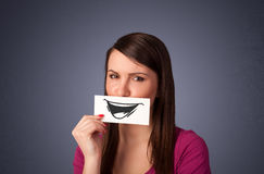 Happy cute girl holding paper with funny smiley drawing Royalty Free Stock Photography
